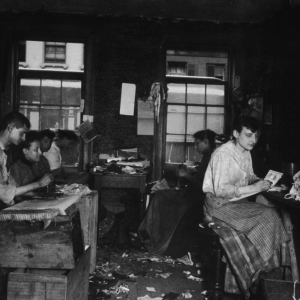 Jacob Riis, Men and women make neckties inside a tenement on Division Street, photograph, Italy, circa1890.